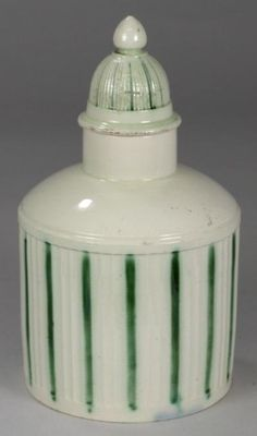 A Creamware Tea Canister (FS17/575) offered in our Three Day Fine Art Sale starting on 29th January 2013 at our salerooms in Exeter, Devon.  A creamware tea canister of Leeds type and of circular vertically fluted form with plain sloping shoulders and raised neck with domed fluted cover with simple green linear decoration, 14cm high, circa 1780.