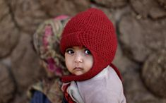 An Afghan refugee girl walks with her sister in a slum on the outskirts of Islamabad, Pakistan, Jan. 13, 2012.