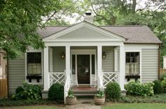 CURB APPEAL -- wood door, light fixtures, pediment, hydrangeas, boxwoods, potted plants