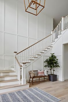 Legacy in Silverleaf- Such a stunning entrance! We love the white wainscoting all the way up the stairwell + the wood entryway bench with a back + tall indoor plant + linen striped rug Staircase Wall Decor, Foyer Staircase, Entryway Stairs, Staircase Remodel, Staircase Design, Staircase Molding, Stairway Wainscoting, Stairwell Wall, White Staircase