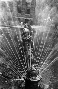 Fire hydrants opened in the summer heat in Harlem, 1963. (photo by Leonard Freed)