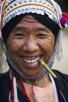 Portrait of woman from Akha tribe smoking a small cigar, Thailand