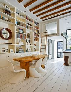 whitewashed wood floors, floor to ceiling built in shelves, exposed beams, high ceilings.