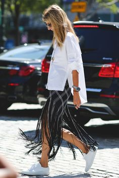 Dress down a dramatic fringe skirt with a classic button-up and all-white sneakers. #refinery29 http://www.refinery29.com/2015/09/93788/ny-fashion-week-spring-2016-street-style-pictures#slide-14