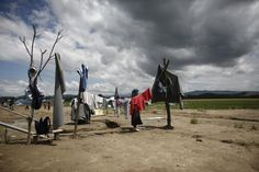 EUROPE-MIGRANTS/GREECE-MACEDONIA A refugee woman hangs clothes to dry at the sun after heavy rainfall at a makeshift camp for migrants and refugees at the Greek-Macedonian border near the village of Idomeni, Greece, May 22, 2016. REUTERS/Kostas Tsironis TPX IMAGES OF THE DAY