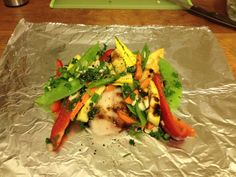 Tear a square of tin foil about 12 x 24″. Fold it in half and place one fish fillet in the center. Add your vegetables on top of the fish, t...