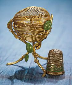 FRENCH MINIATURE GILT BOX AS THIMBLE HOLDER WITH MATCHING THIMBLE Designed to appear as a twig with bird nest containing a nest,the gilt metal fancy is decorated with green enamel leaves,and the egg hinges open to hollow interior which contains a gilt thimble with green painted decorations. French,circa 1870.