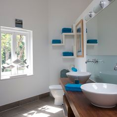 love the quirky bathroom shelves and pop of blue!