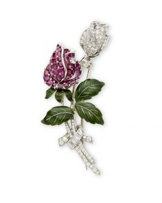 A Diamond, Ruby and Enamel Rose Brooch, by Oscar Heyman & Brothers, Circa 1937. Designed as two rosebuds, one a pavé-set diamond rosebud, the other set with calibré-cut rubies and diamond detail, with green enamel leaves and diamond-set stem and ribbon. Mounted in platinum.