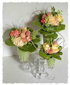 Three separate arrangements in different sized wine glasses - Several layers of Bergenia leaves make a collar - around a small posy of pale peach Roses and Carnations, deeper peach spray Carnations, Meconopsis cambrica seed pods (Welsh Poppy), Alchemilla mollis, Solidago (Golden Rod),  Asparagus officinalis and some Lychee fruits ~ Chrissie Harten (DESIGN 55)