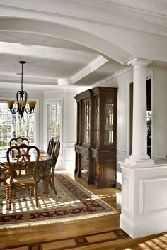 Column on a half wall with ornamentation...arch? Separate ceiling heights...end moulding...