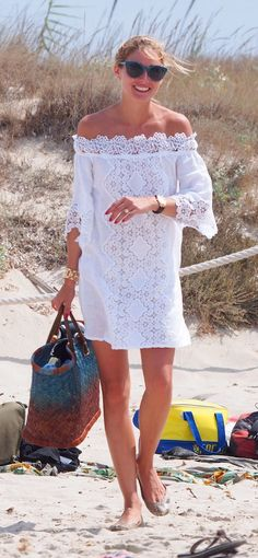 Olivia Palermo styled her Temptation Positano dress with a woven ombré beach bag, Dior cat-eye sunglasses, and a handful of her wear-with-anything accessories, including gold jewels and a black chunky watch.