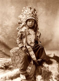 This photograph shows a nice example of Sioux Indian Beadwork. The photo shows James Spotted Elk, a Sioux Indian Boy. He is pictured in an ornate Beaded vest. This is a nice example of this type of work. The picture was taken in 1900.