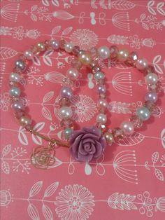 pulseras perlas de colores y flor lila
