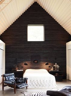 Soaring ceilings are highlighted when a single wall is painted black and left nearly free of adornment.