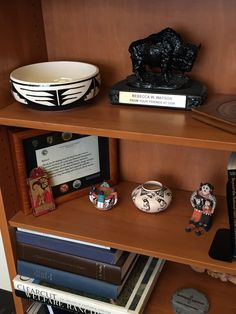 Pottery and collectibles lively up this office bookshelf.
