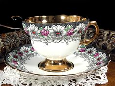 Rosina Daisy Chintz Teacup and Saucer, Gold Banded Floral Tea Cup Made in England This is a superb gold banded cup with a grey daisy chintz exterior. From the darling scalloped edge saucer to the gold