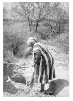 Maricopa woman digging clay with which to make pottery - circa 1940