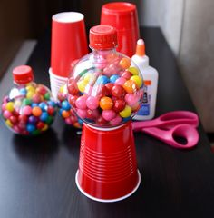 Round Coke bottle filled with gumballs, glued atop a red cup.