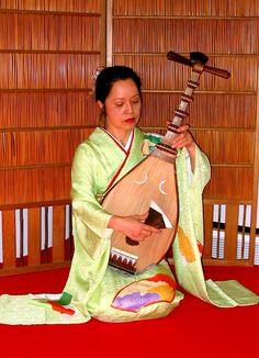 The instrument is a Biwa, or short-necked lute.