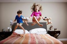 Two Children Jumping on a Bed with Stuffed Animals - Cavan Images/Taxi/Getty Images