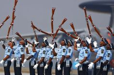 Indian Air Force soldiers toss their rifles