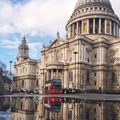 A little red bus makes its way past the towering  StPauls Cathedral.   by @sparrowflu.