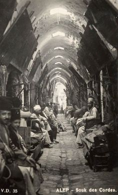 Aleppo Syria 1920 a real-photo postcard by Armenian photographer V. Deroian of shop owners sitting outside their individual stores at Aleppo
