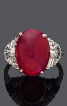 AN ART DECO PLATINUM, BURMESE RUBY AND DIAMOND RING, CIRCA 1930.  Set to the centre with an oval, treated Burmese ruby cabochon weighing 7.80 carats, flanked by baguette- and single-cut diamonds. #ArtDeco