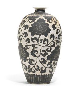 Lot 67| Sotheby's London. ROPERTY FROM A JAPANESE COLLECTION A RARE 'CIZHOU' SGRAFFIATO MEIPING SONG DYNASTY the ovoid body rising from a recessed base to a rounded shoulder and barrow short waisted neck with everted dished mouth, freely carved through the layer of brown slip to the ivory-white layer beneath with a broad leafy peony scroll band between bands of overlapping radiating petals encircling the base and neck, the recessed base covered with a pale buff slip 32.5cm., 12 3/4 in.