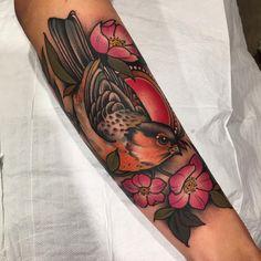 Tatuagem feita por Ag Tattoo de São Paulo. Pássaro com flores rosas no braço.