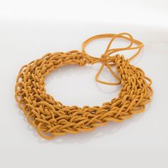 """""""Intreccio zafferano"""" is an handmade necklace, made of cotton cable and nylons, fingers interlaced. The particular production makes this optional soft and light. 100% made in Italy. Weight: 49 gr. Color: saffron."""