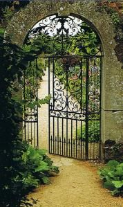 Wrought iron gate set into stone wall  at Rousham House, Oxfordshire, via Trouvais.