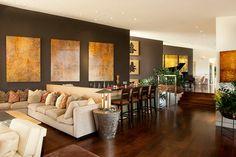 un foyer splendide, sofas couleur crème, un plancher marron foncé, peintures murales à thème occidental