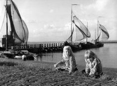 Twee meisjes in Markense klederdracht wieden onkruid in de haven. 1950