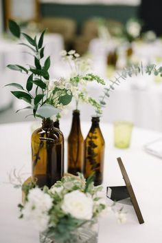 Industrial Modern Wedding with a Greenery Wall Amber bottle centerpieces - Photo by The Kama Photogr Wedding Table Centerpieces, Flower Centerpieces, Centerpiece Ideas, Beer Bottle Centerpieces, Modern Centerpieces, Greenery Centerpiece, Wedding Wall Decorations, September Wedding Centerpieces, Simple Wedding Table Decorations