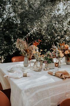 Linen reception tables with orange velvet chairs + rust flowers in mismatched vases | Image by Lauren Mecum
