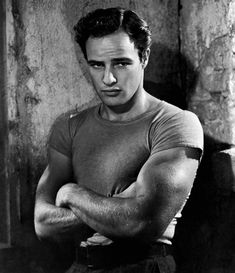 Sporting a side-part, Marlon Brando poses for a photo.
