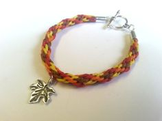 A handmade toggle bracelet made from a kumihimo braid of colours inspired by Autumn, with a choice of charm.