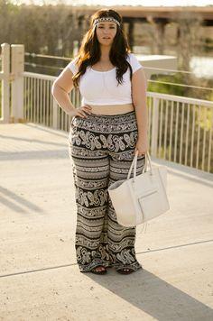 Chica curvi usando un crop top en color blanco con un pantalón con estampados