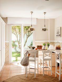 Office con mesa en L, taburetes altos y muebles en blanco, con suelo de toba, alfombra de fibra natural y salida al jardín