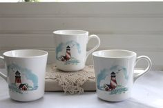 Presenting a set of three (3) Corelle by Corning stoneware coffee cups in the collectable Lighthouse pattern. These cups would be a wonderful