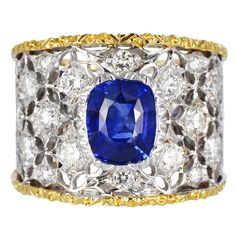 BUCCELLATI   1.40ct. Cushion cut Blue Sapphire set with 1.00ct. Full cut Diamond accents.Two tone 18K Yellow and White Gold open work Ring    , signed M. Buccellati.