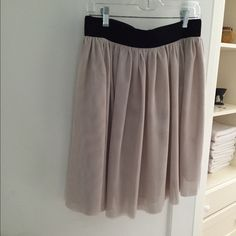 Cream colored full skirt with elastic waist Very full and flowy. Chiffon material. Lined. Cream color. Comfortable and adjustable because of striking thick black waistline. Nice for hot weather. No buttons or snaps. Waistband is elastic all the way around. Wear with a crop top or tuck in a blouse. Special occasion or work. Falls around the knee depending on your height. Excellent condition. Hardly worn. burlapp Skirts A-Line or Full
