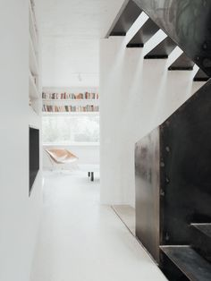 Dark black steel stairs stand out against the white walls in this modern home.