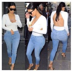 Kim Kardashian. Denim, white long sleeved open backed shirt. Gold heels.