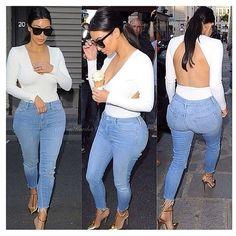 Kim Kardashian. Denim, white long sleeved open backed shirt. Gold heels.