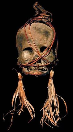 DAYAK TRIBE:  HEAD HUNTING HUMAN TROPHY SKULL  BOUND HUMAN BONE, VEGETABLE MATTER, BAMBOO  THE DAYAK TRIBE, FROM BORNEO ISLAND  INDONESIA, CARVE DESIGNS INTO THE SKULLS  OF THEIR HEADHUNTED VICTIMS AND INSERT WOODEN FIGURES.