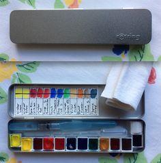 Voici ma nouvelle boîte d'aquarelle. Une boîte de stylos, des demi-godets d'aquarelle et un peu de scotch double face pour les faire tenir à l'intérieur. Here is my new watercolor box. A box of pens, watercolor half pans and some double-sided tape to hold them inside.
