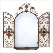 """Imagine the possibilities! Gorgeous scrollwork wall decoration brings to mind the gates of a splendid Tuscan garden; a generous mirror and curio shelf add lavish designer flair. Mirror: 15"""" x 23""""; shelf space: 3 1/2"""" deep.  Weight 10.8 lbs. Metal..."""